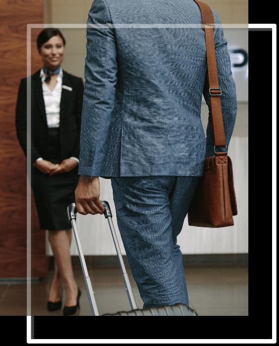 Client avec une valise, et réceptionniste d'hôtel