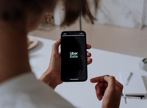 Main tenant un smartphone avec Uber Eats